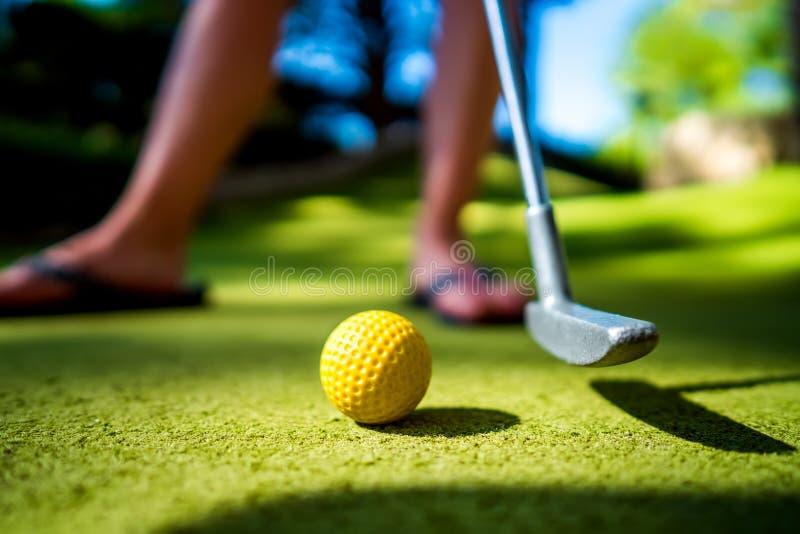 Mini Golf amarela a bola com um bastão no por do sol fotografia de stock royalty free