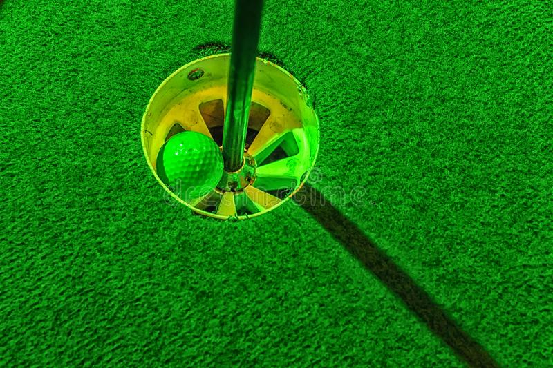 Mini golf ball inside the hole stock images
