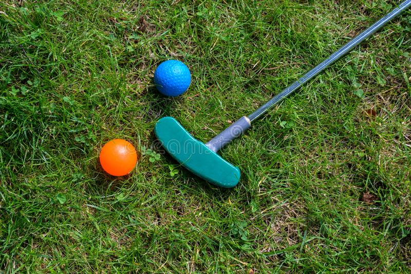 Mini golf equipment, balls and a club on the grass, high angle view from above, copy space stock image