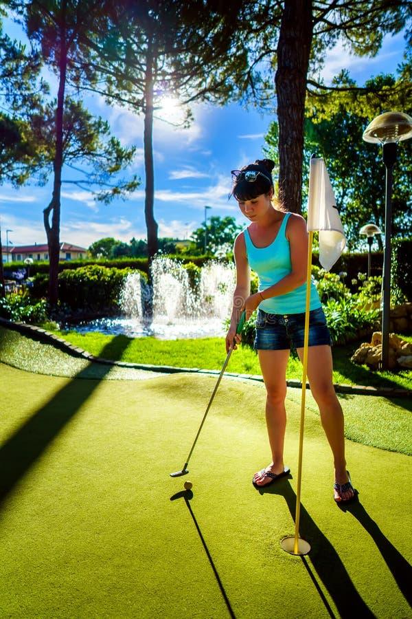Mini Golf - Frau, die Golf auf grünem Gras bei Sonnenuntergang spielt lizenzfreies stockfoto