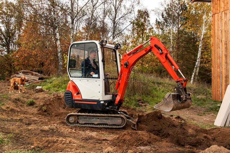 Mini- grävskopa på konstruktionsplats Grävskopan reglerar terrängen runt om huset fotografering för bildbyråer