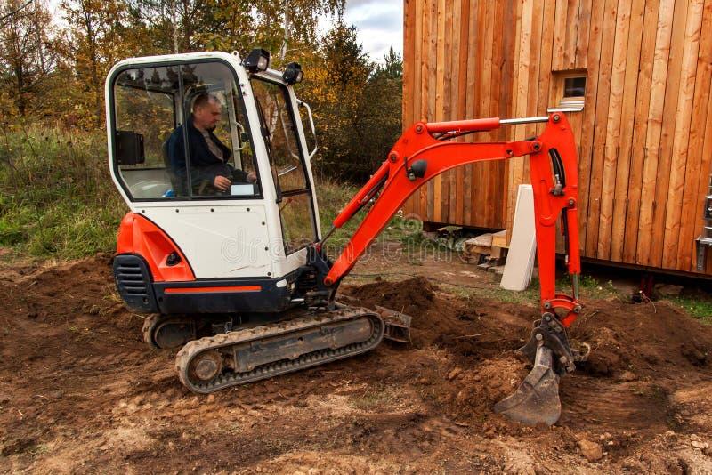 Mini- grävskopa på konstruktionsplats Grävskopan reglerar terrängen runt om huset royaltyfria bilder