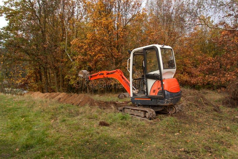 Mini- grävskopa på konstruktionsplats Konstruktion av ett familjhus nära en skog arkivbild