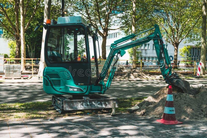 Mini- grävskopa som arbetar på vägen Amsterdam Buitenveldert fotografering för bildbyråer