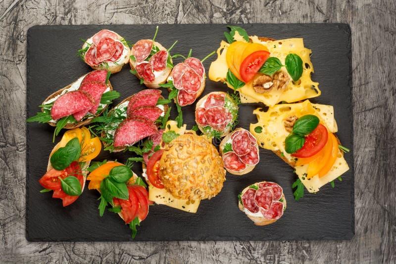 Mini grupo do alimento dos sanduíches Brushetta ou tapas espanhóis tradicionais autênticos para a tabela do almoço Petisco delici imagens de stock