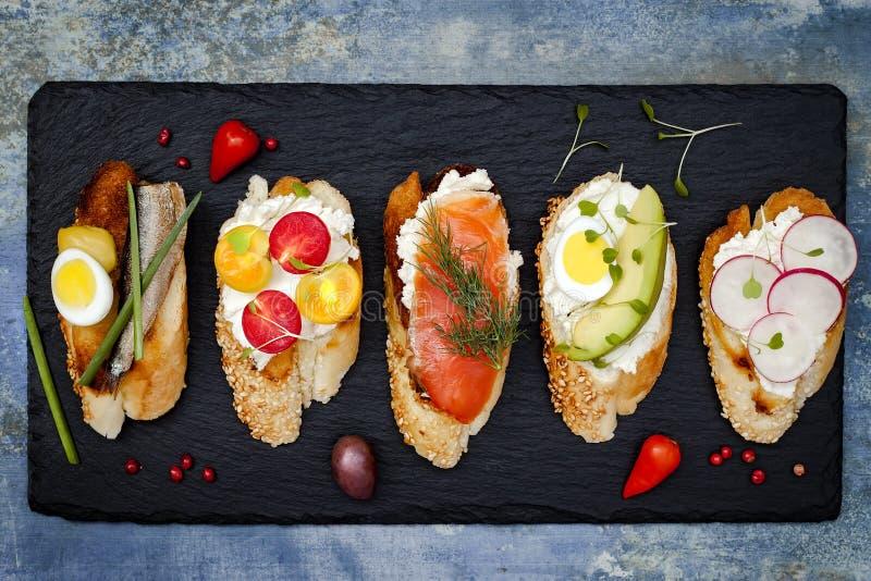 Mini grupo do alimento dos sanduíches Brushetta ou tapas espanhóis tradicionais autênticos para a tabela do almoço Petisco delici foto de stock