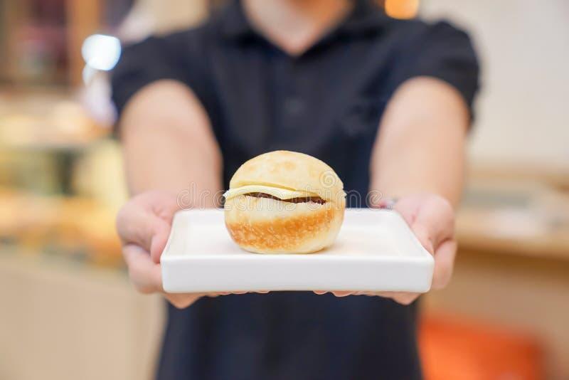 Mini Hamburger no prato quadrado cer?mico branco com terra arrendada da m?o fotos de stock royalty free