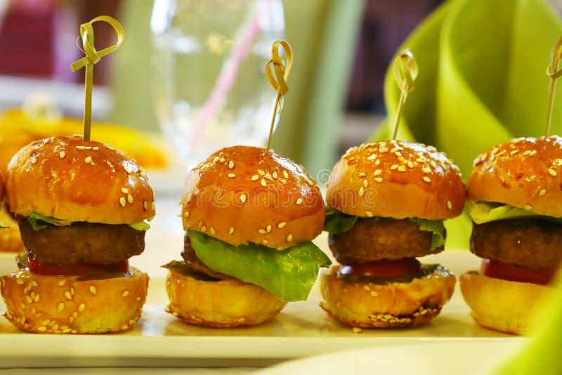 Mini hamburger with salad leaf served on plate. Mini hamburger with salad leaf served on the plate on restaurant table royalty free stock photo