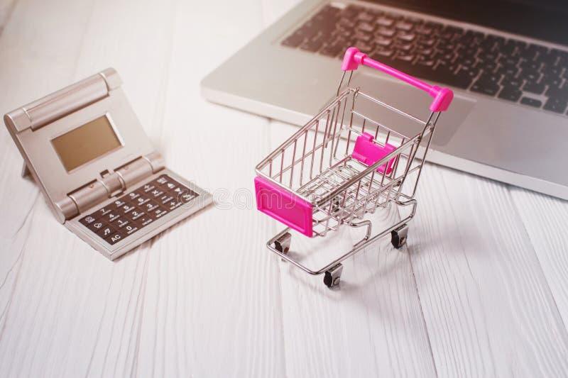 Mini het winkelen karretje, laptop, calculator op een wit houten bureau royalty-vrije stock fotografie