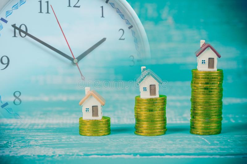 Mini house on coin stack or money. With clock royalty free stock photo