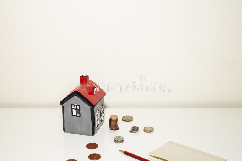 Mini house model coins. Saving money for property concept. Red roof House model, coins, pencil note book. Copy space royalty free stock images