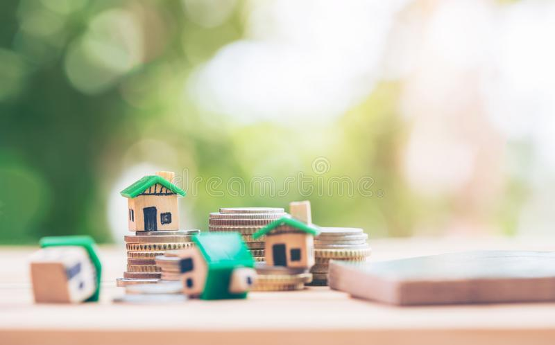 Mini house model and stack of coins. Business risk management stock photography
