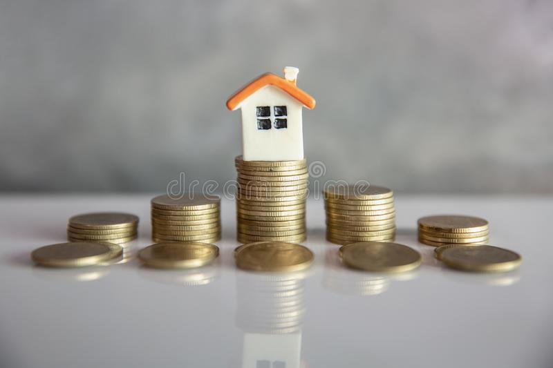 Mini house on stack of coins. Concept of Investment property and Risk Management stock photo