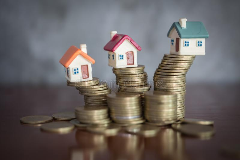 Mini house on stack of coins, Concept of Investment property, Investment risk and uncertainty in the real estate housing market.  royalty free stock image