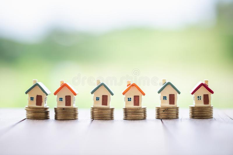 Mini house on stack of coins, Concept of Investment property, Investment risk and uncertainty in the real estate housing market royalty free stock photography