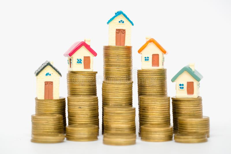 Mini house on stack of coins, isolated on white background, Concept of Investment property royalty free stock photo
