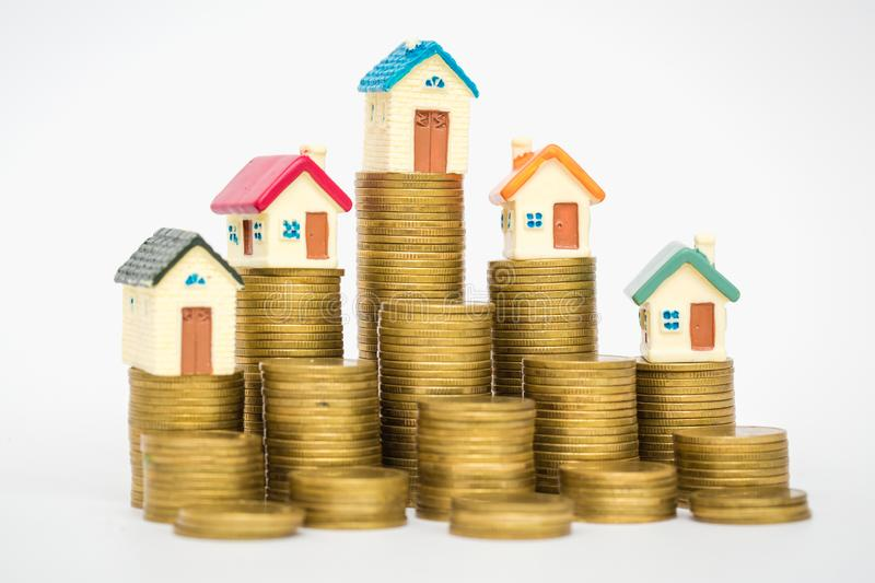 Mini house on stack of coins isolated on white background, Real estate investment, Save money with stack coin, Business growth royalty free stock image