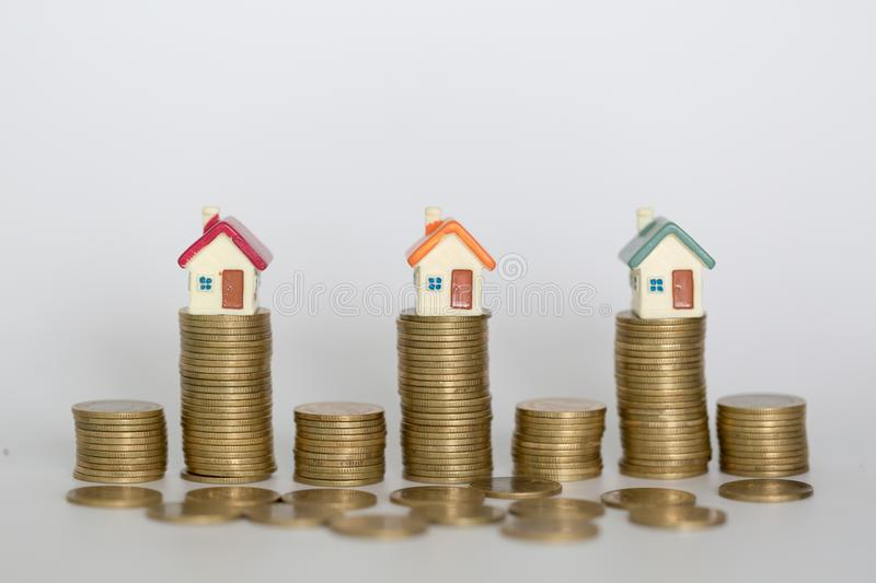 Mini house on stack of coins,Money and house, Real estate investment, Save money with stack coin, Mortgage concept. Isolated stock images