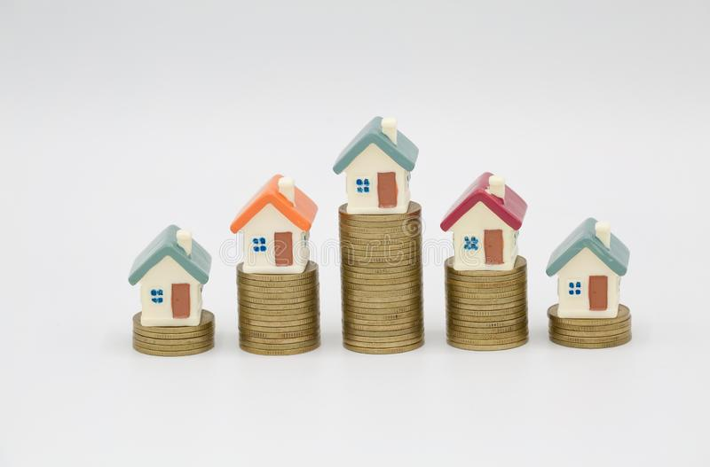 Mini house on stack of coins on white background., Concept of Investment property, Investment risk and uncertainty in the real royalty free stock photos
