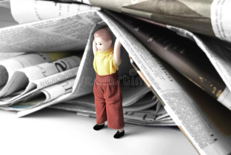 Mini Human Figure of Man or Child Holding Heap of Newspapers stock photography