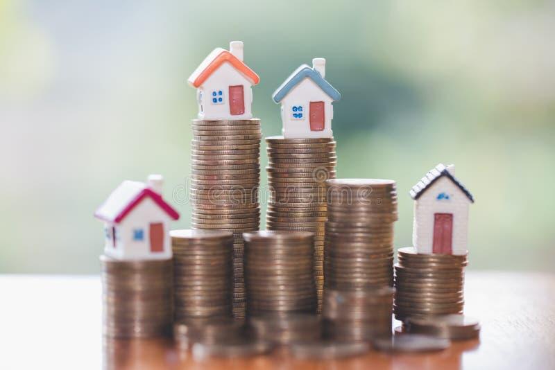 Mini- hus på bunten av mynt, fastighetsinvestering, räddningpengar med buntmynt-, affärstillväxtinvestering och finansiellt, royaltyfri foto