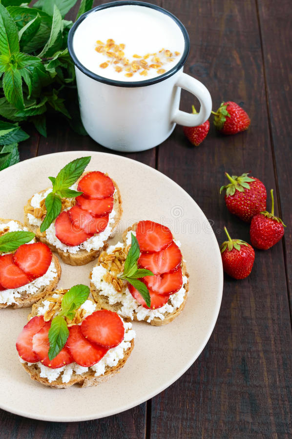 Mini kanapki z chałupa serem, świeżymi truskawkami dekorującymi z nowymi liśćmi na, żyto chlebie i kubku jogurt na zmroku zalecaj obrazy stock