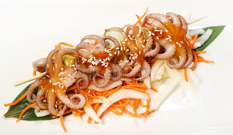 Mini- kebaber på steknålen med kortkort-bläckfiskar och purjolöken som tjänas som i Teriyaki sås, med Pekingkål, morötter och ses arkivbild