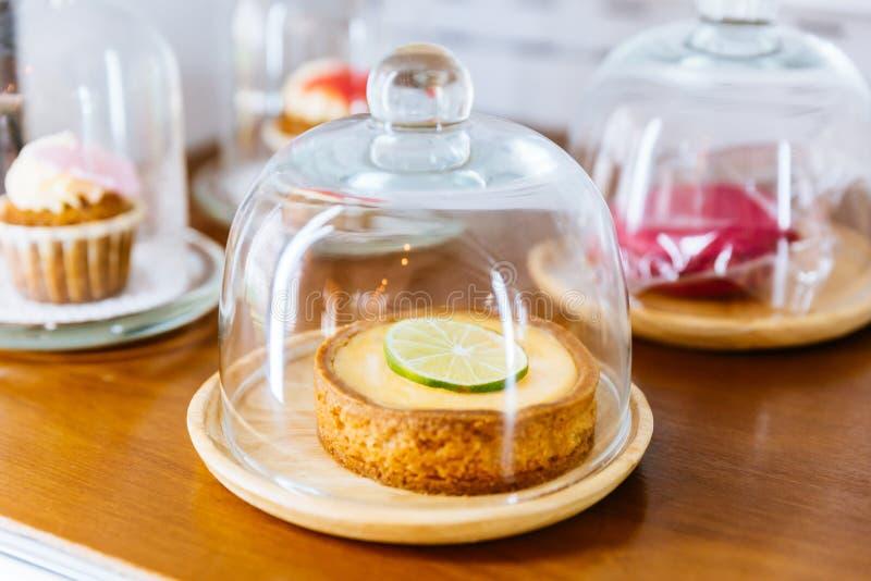Mini Key Lime Pie, der mit Scheibe des Kalkes in der hölzernen Platte und in der Abdeckung mit Glasglasglocke übersteigt stockfotos