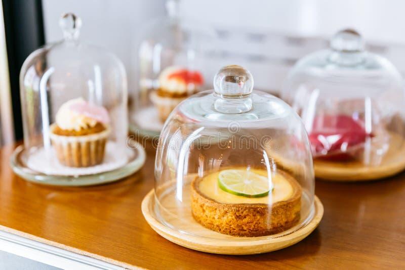 Mini Key Lime Pie polewa z plasterkiem wapno w drewnianym talerzu i pokrywie z szklanym cloche zdjęcie royalty free