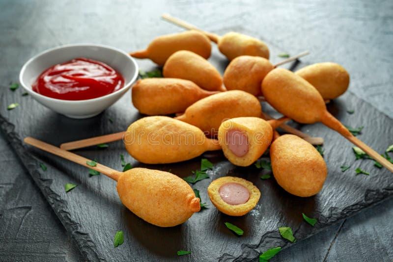 Mini Kukurydzani psy na kamiennym półmisku z ketchupem obrazy stock