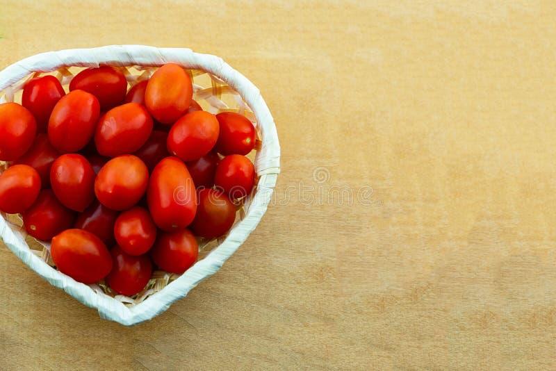 Mini légumes rouges de tomate beaucoup de fruits dans une conception culinaire de l'espace de copie de forme de coeur de panier photos libres de droits