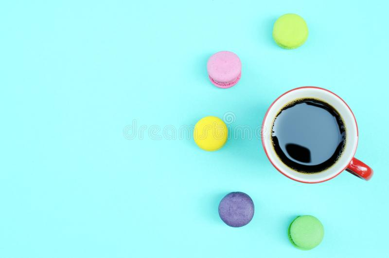 Mini macaroons and black coffee red cups on blue lights backgrounds above, Top views stock photography