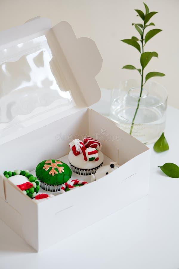 Mini magdalenas del postre de la Navidad festiva estacional en elementos decorativos verdes rojos tradicionales de los símbolos fotografía de archivo