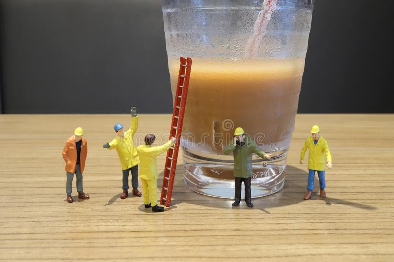 The mini male workers figure with cold drink. A mini male workers figure with cold drink royalty free stock photos