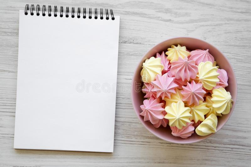 Mini- marängar i en rosa bunke och mellanrumsanteckningsbok över vit träbakgrund, bästa sikt Lekmanna- lägenhet, över huvudet, fr arkivbilder