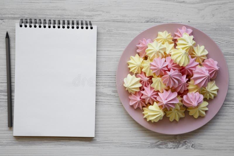 Mini- marängar på den rosa plattan och den tomma notepaden på en vit träbakgrund, bästa sikt Närbild Utrymme för text royaltyfri bild