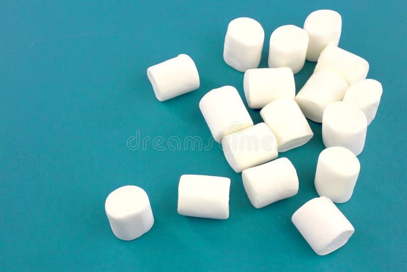 Mini melcochas en un fondo azul modelo geom?trico de las melcochas blancas foto de archivo libre de regalías