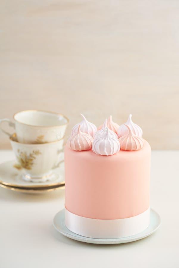 Mini meringue kisses. Mini fondant covered cake with meringue kisses stock photography