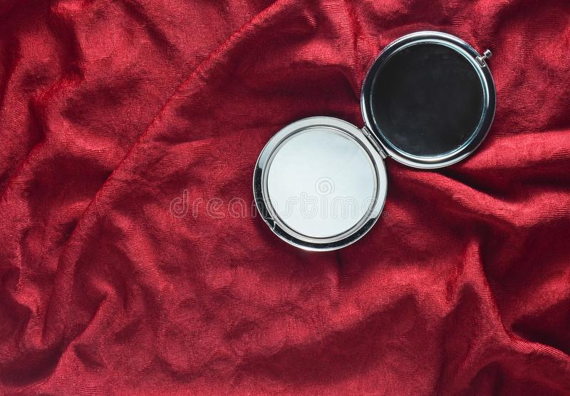 Mini mirror on a red silk background. Items from the women`s cosmetic bag. Top view stock photo