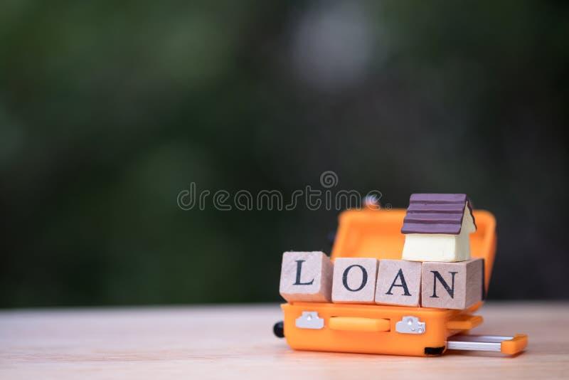 Mini modello della casa in bagagli arancio concetto della proprietà del bene immobile di ipoteca fotografie stock