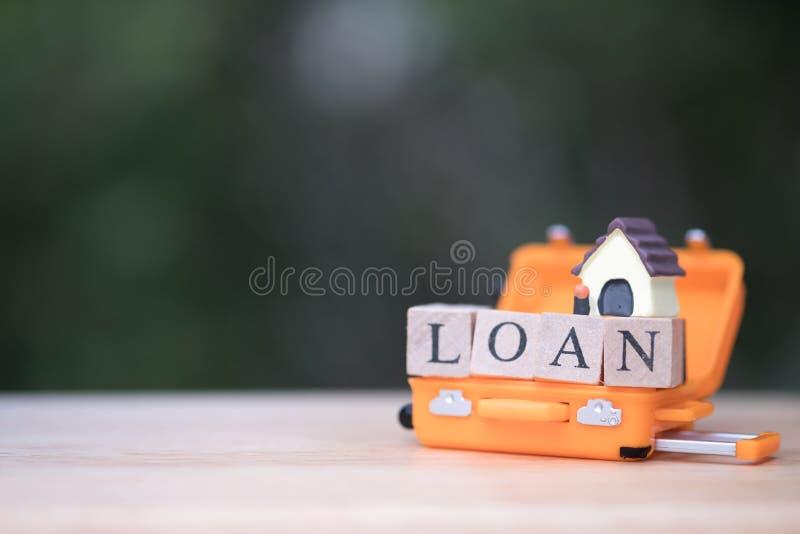 Mini modello della casa in bagagli arancio concetto della proprietà del bene immobile di ipoteca fotografia stock libera da diritti