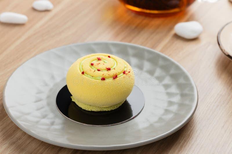Mini- moussekaka som täckas med gul chokladvelour på grå färger pl arkivbilder
