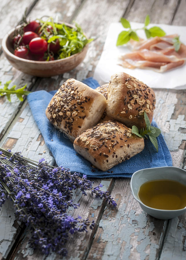 Mini nieociosany chleb z lavand kwiatem na stronie, oliwa z oliwek, różanym winie, czereśniowych pomidorach i prosciuto, zdjęcia stock