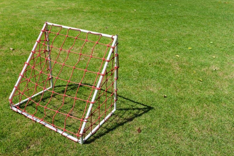 Mini objetivo pequeno do futebol para crianças com rede vermelha no verde imagens de stock royalty free