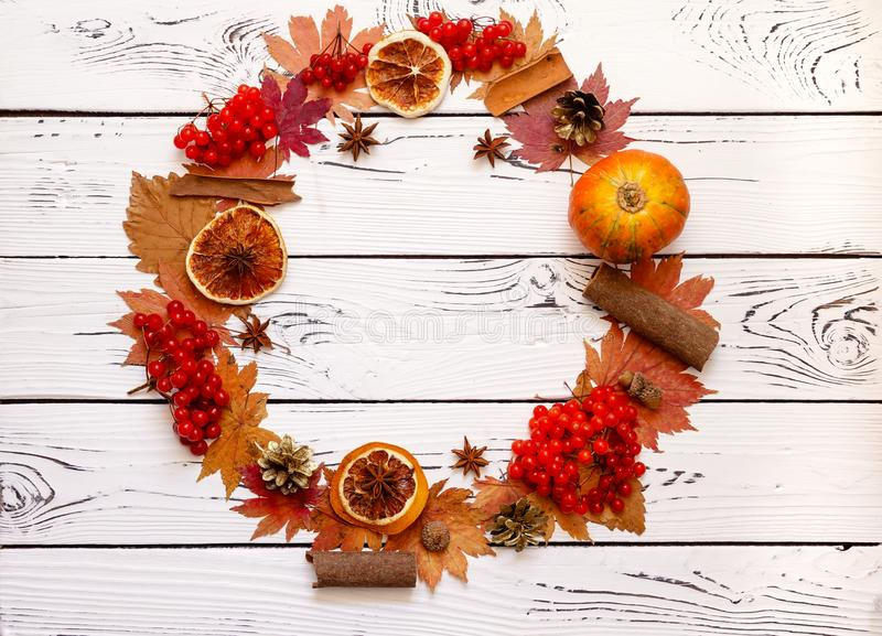 Mini orange pumpkin, dehydrated orange slices, red maple leaves, and arrow-wood berries form a wreath on a brown rustic wooden royalty free stock photo