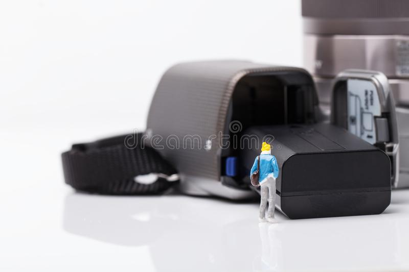 Mini people model checking digital camera for travel royalty free stock image
