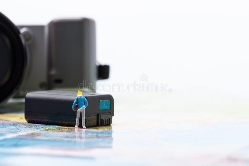 Mini people model checking digital camera for travel stock image