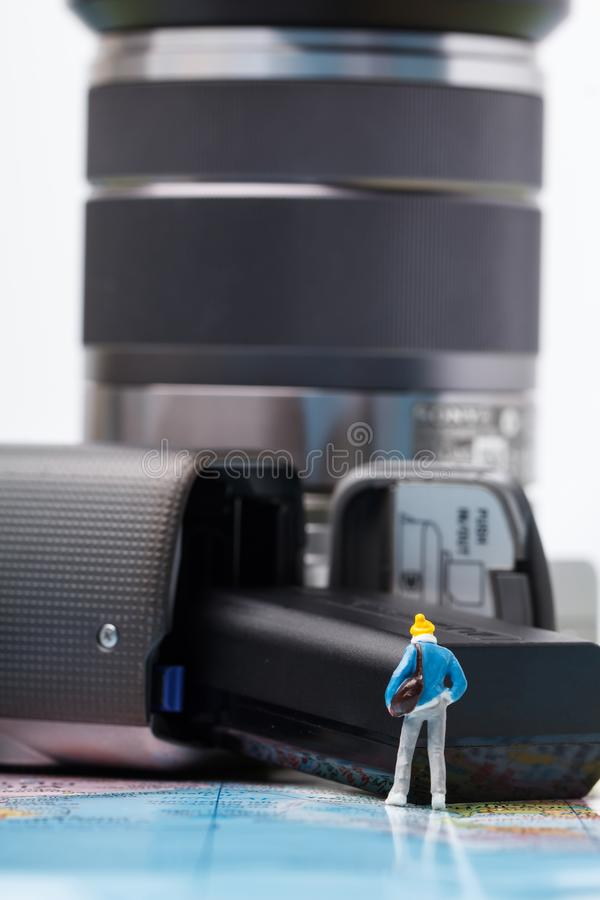 Mini people model checking digital camera for travel stock photography