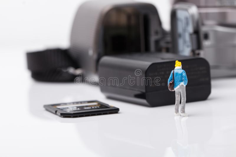 Mini people model checking digital camera for travel royalty free stock images