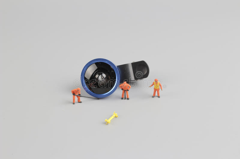 mini people worker cleaning camera len stock image